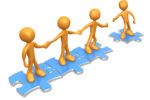 Team Of Three Orange People Holding Hands And Standing On Blue Puzzle Pieces, With One Man Reaching Out To Connect Another To Their Group Clipart Illustration Graphic