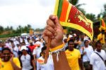 A Sri Lankan man waves the national flag during a charity walk that ended in Sri Lanka's northern most tip of Point Pedro on July 27, 2011. The 27-day walk was organised by local charity, the Colours of Trust, to raise USD2 million to build a cancer unit in the former northern war-hit Jaffna hospital. Sri Lanka's former cricket captain Mahela Jayawardene, who lost his younger brother to cancer, also participated in this walk.   TOPSHOTS    AFP PHOTO/Ishara S. KODIKARA (Photo credit should read Ishara S.KODIKARA/AFP/Getty Images) [PNG Merlin Archive]